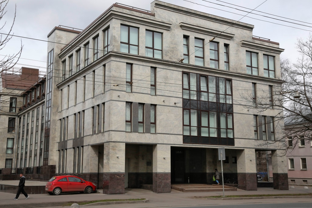 """Image: A women enters a four-story building known as the """"troll factory"""" in St. Petersburg"""