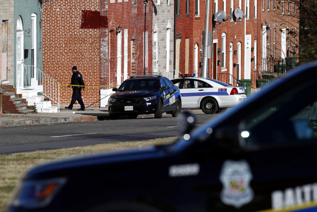 Image: An officer walks behind a police line near the scene of a shooting