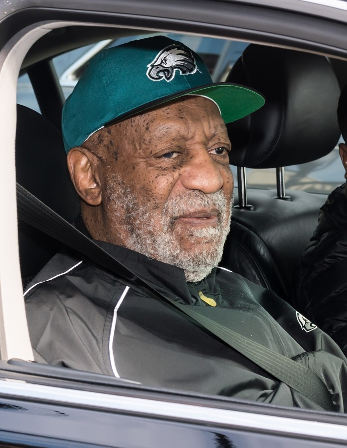 Image: Bill Cosby, wearing Philadelphia Eagles apparel, sits in a car