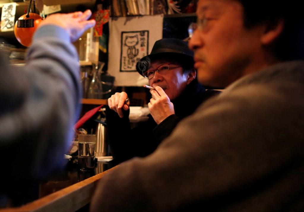 Image: A man smokes at a tavern in Tokyo