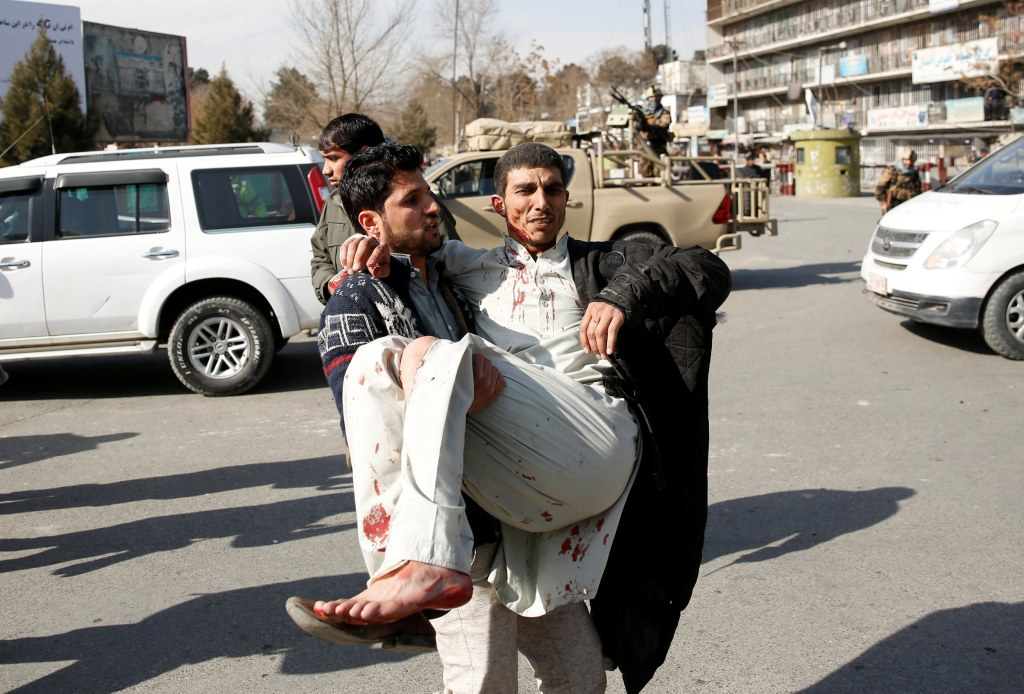 Image: Injured man is carried after a blast in Kabul