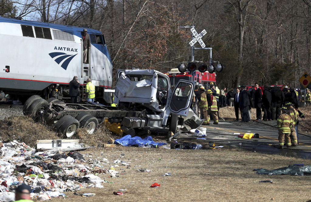 Image: Emergency personnel work at the scene of a train crash