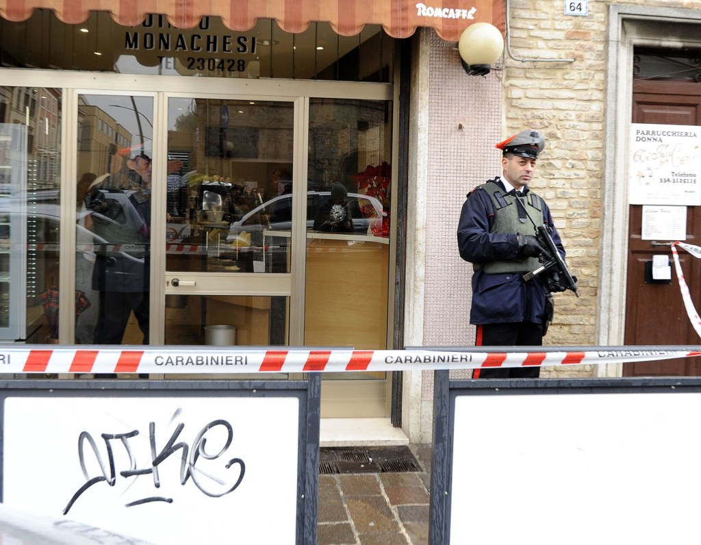 Image: Police officers stand guard as forensics officers carry out investigations in the area following the wounding of several foreign nationals in a drive-by shooting at Macerata, on Feb. 3, 2018.