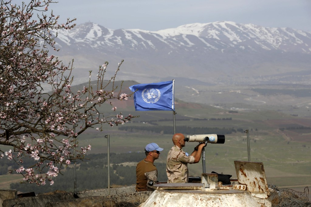 Image: UN members look through binoculars as they monitor the Israel-Syria border in the Israeli-annexed Golan Heights, on Feb. 10, 2018.