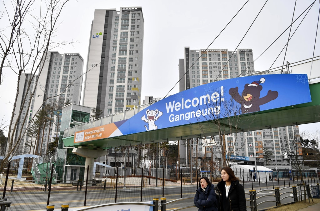 People walk near a gate of the athletes' village for the Pyeongchang Winter Olympics in Gangneung on Jan. 31, 2018. Kyodo / AP