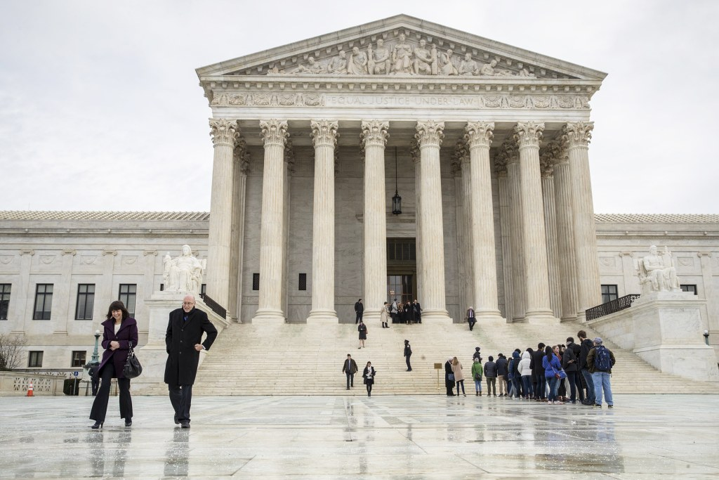 Image: People stands on the plaza of the U.S. Supreme Court in Washington to attend arguments