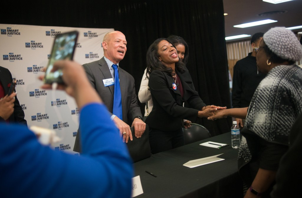 Image: Dallas County district attorney candidates, Judge John Creuzot, left, and Judge Elizabeth Frizell shake hands with members of the audience