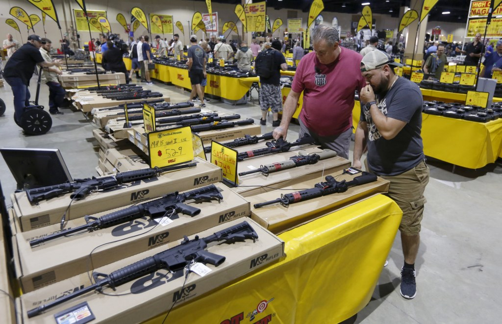 Image: With a variant of the AR-15 in the foreground, patrons peruse weapons at a gun show in Miami, Florida on Feb. 17, 2018.