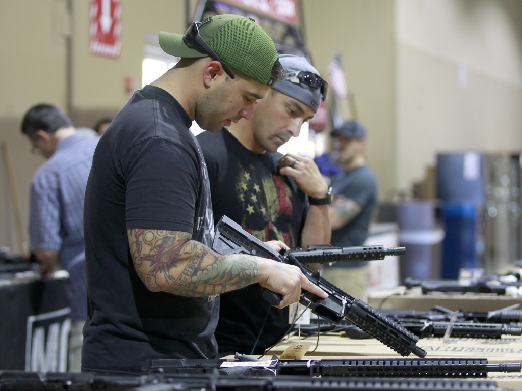 Image: Patrons peruse weapons at a gun show in Miami, Florida, Feb. 17, 2018.