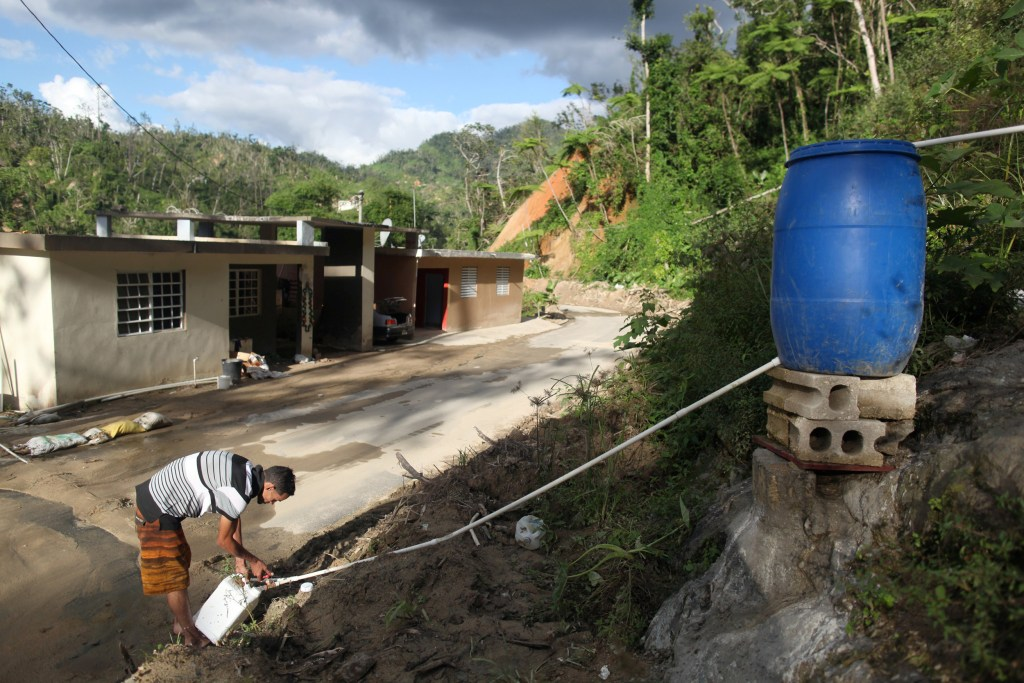 Image: Juan Cosme fills a container with mountain spring water outside his home, after Hurricane Maria hit the island in September 2017, in Utuado