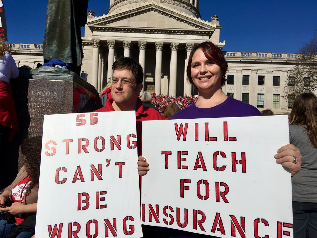 "Image: Teacher John and Kerry Guerini of Fayetteville, West Virginia, holding sign ""title ="" Image: Teacher John and Kerry Guerini of Fayetteville, West Virginia, holding signs ""/> </a></p> <p><figcaption class="