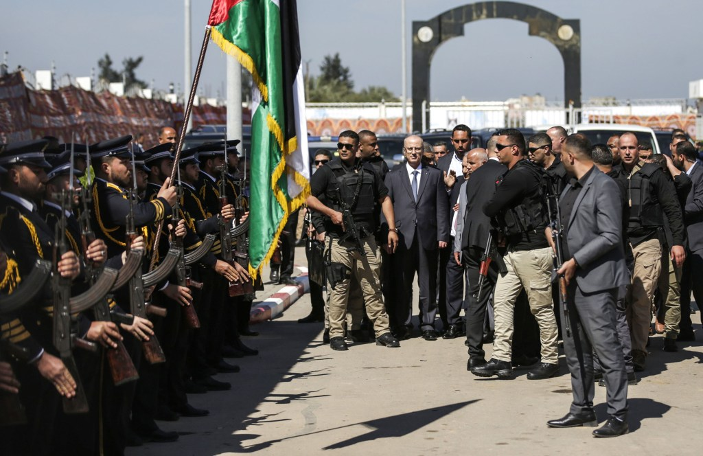 Image: Palestinian Prime Minister Rami Hamdallah is greeted by police forces