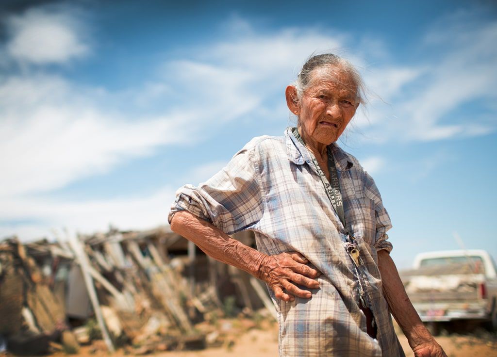Anna Begay stands near her home on the Navajo reservation. She received a small solar array from Eagle Energy and now uses it to provide light after t...