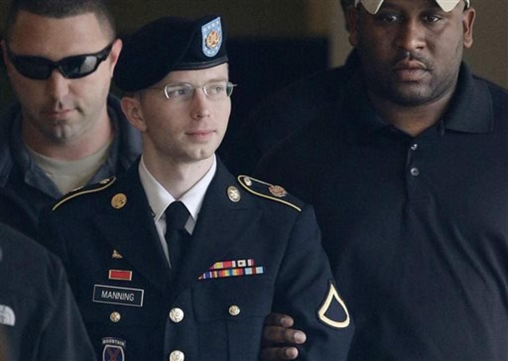 FILE - In this Tuesday, Aug. 20, 2013 file photo, Army Pfc. Bradley Manning is escorted to a security vehicle outside a courthouse in Fort Meade, Md.,...