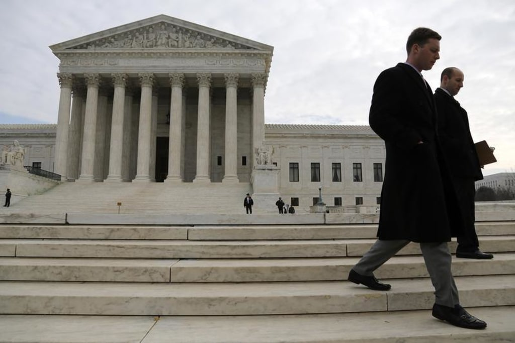 IMAGE: People walk outside the U.S. Supreme Court