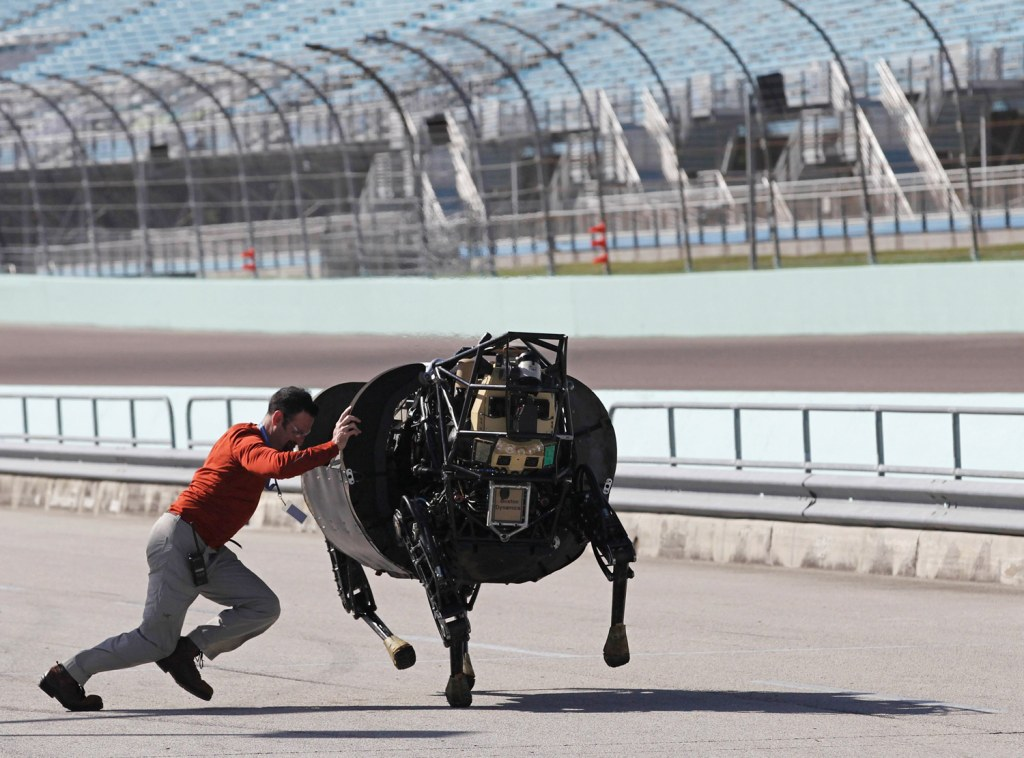 An unidentified LS3 team member shoves an LS 3 (Legged Squad Support System) robot that was galloping off course, back on track during a high-speed de...
