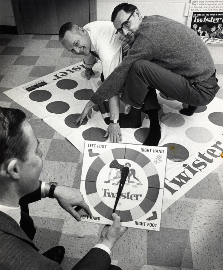 """In a Dec. 16,1966 photo, co-inventors of the game """"Twister"""" Charles Foley, left, and Neil Rabens demonstrate the game for Charles McCarty, foreground, president of Research and Development, Inc., in Minnesota."""