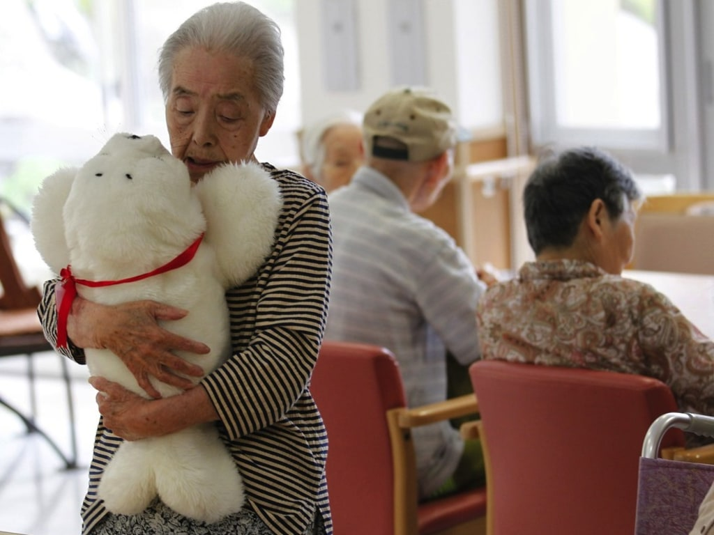 Satsuko Yatsuzaka (84) holds a therapeutic robot named Paro at the Suisyoen retirement home, about 30 km (19 miles) south of the tsunami-crippled nucl...