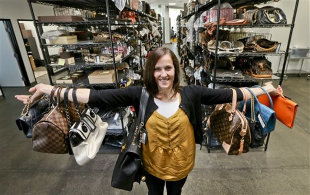 This photo taken May 2, 2013, shows Sarah Davis, co-owner of Fashionphile.com, posing with her bags in a company warehouse in the Carlsbad, Calif. The...