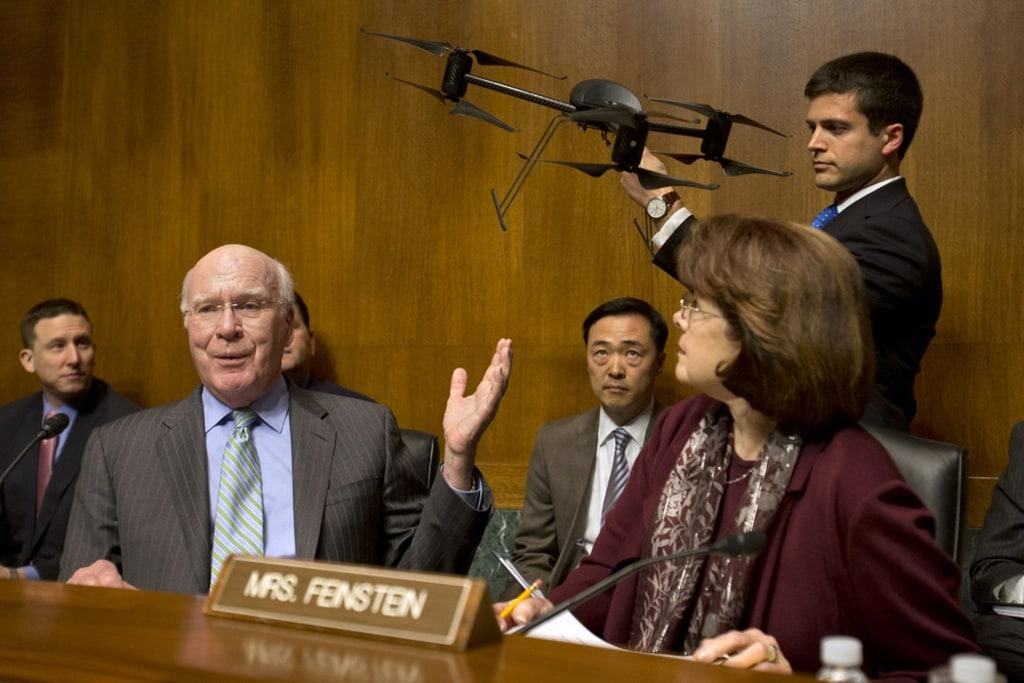Senate Judiciary Committee Chairman Sen. Patrick Leahy, D-Vt., left, gestures to an example of a drone held by a staff member, on Capitol Hill in Wash...