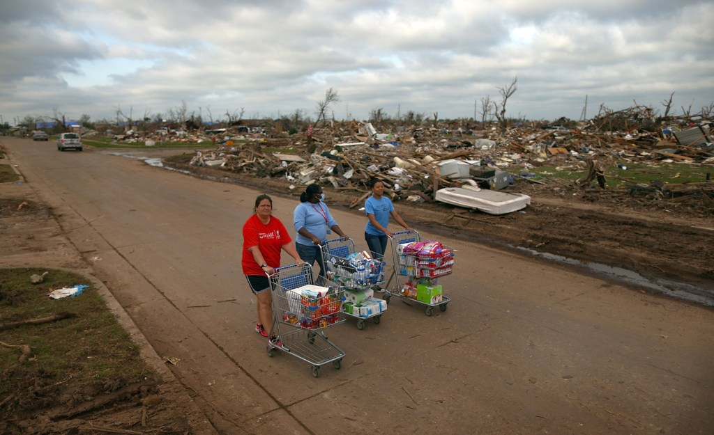 Image: Volunteers Jaqi Castro, Angelica Morris-Smith and Cetoria Petties walk through a tornado ravaged neighborhood handing out s...