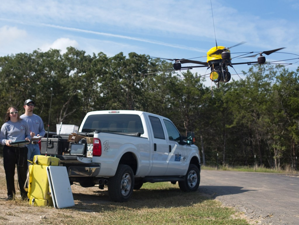 Doctoral candidate Brittany Duncan, center, flies an unmanned aerial vehicle at Disaster City in College Station, Texas on Friday, Sept. 28. On either...