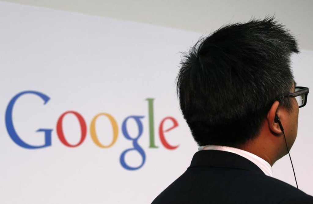 """A man stands in front of a Google logo before a talk titled """"Connecting with the World Empowering Young Entrepreneurs for the New Digital Age"""" by Goog..."""