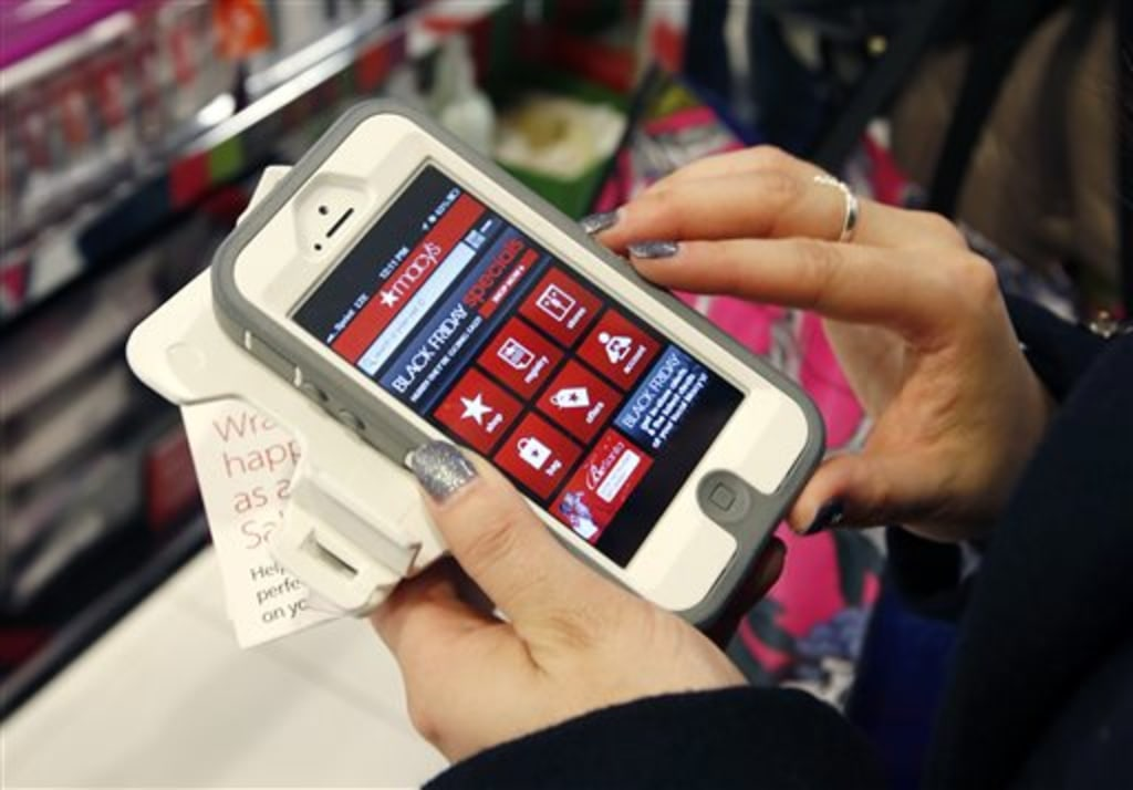 Tashalee Rodriguez, of Boston, uses a smart phone app while shopping at Macy's in downtown Boston.
