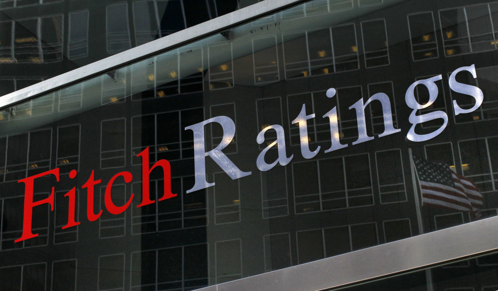 A flag is reflected on the window of the Fitch Ratings headquarters in New York in this Feb. 6, 2013, file photo. Fitch Ratings warned on Tuesday that it could cut the sovereign credit rating of the United States from AAA, citing the political brinkmanship over raising the federal debt ceiling.