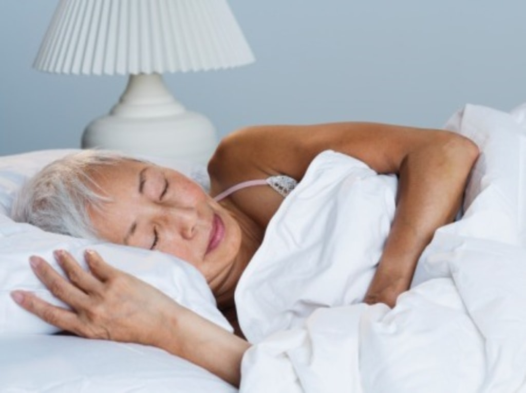 Senior Asian woman sleeping in bed. People, Bed, Horizontal, Indoors, High Angle View, Front View, Head And Shoulders, Asian Ethnicity, Bedroom, Lying...