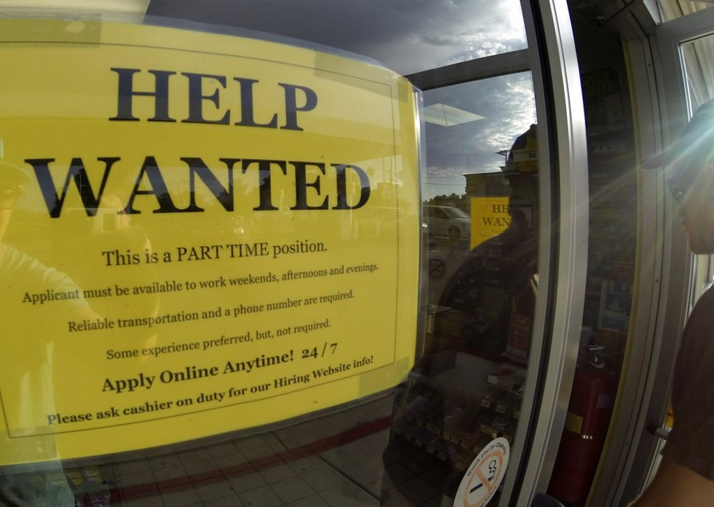a help wanted sign is posted on the door of a gas station in encinitas