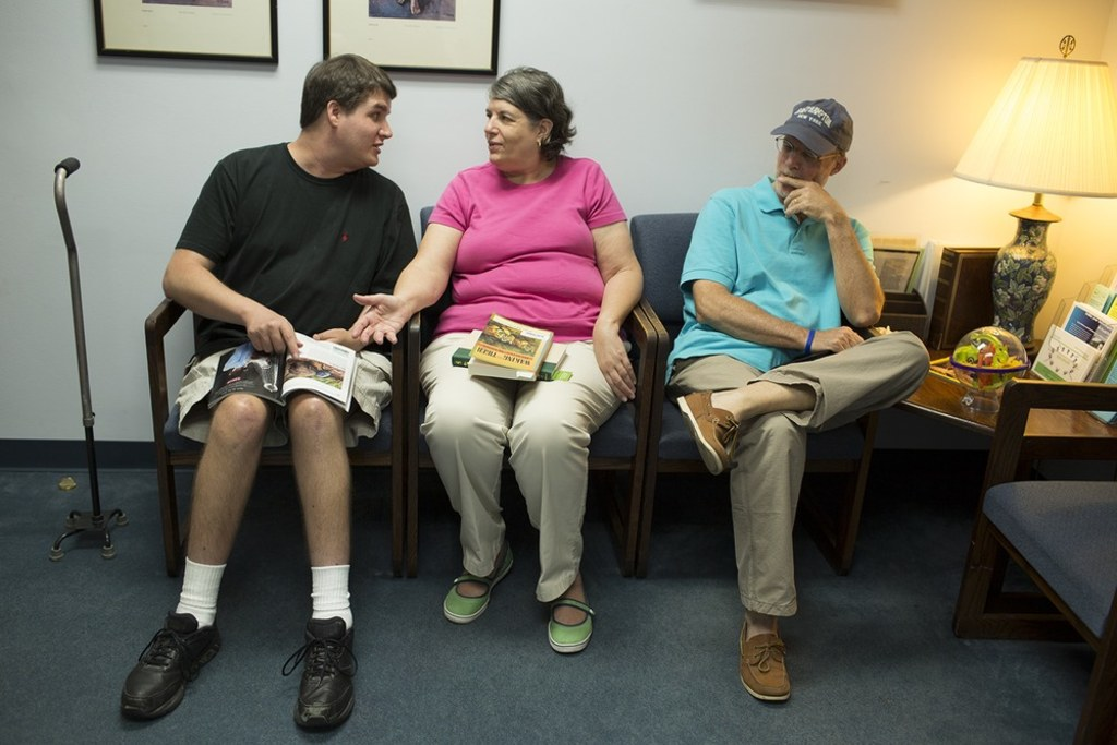 Mac Fedge, left, sits with his parents Kathy and Don Fedge