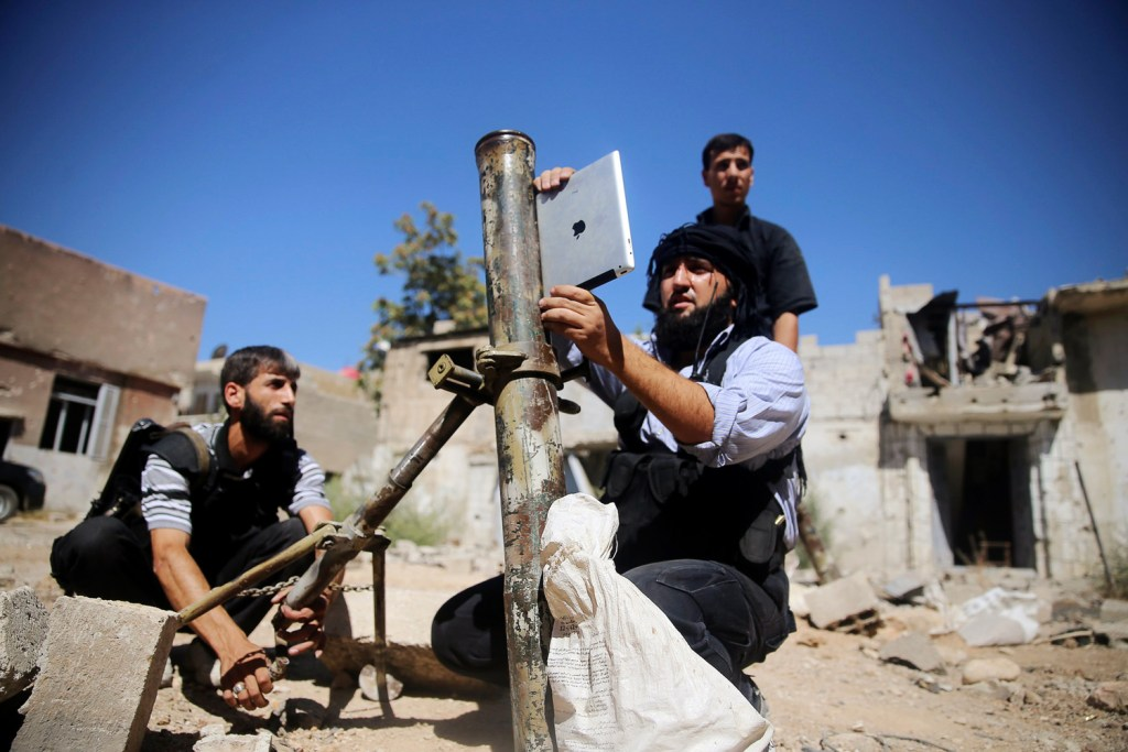 A member of the 'Ansar Dimachk' Brigade, part of the 'Asood Allah' Brigade which operates under the Free Syrian Army, uses an iPad during preparations...