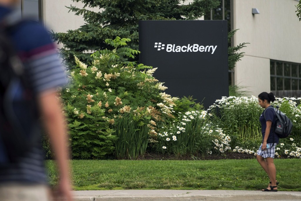 FILE- In this Tuesday, July 9, 2013, file photo, pedestrians walk near BlackBerry's headquarters in Waterloo, Ontario, on the morning of the company's...