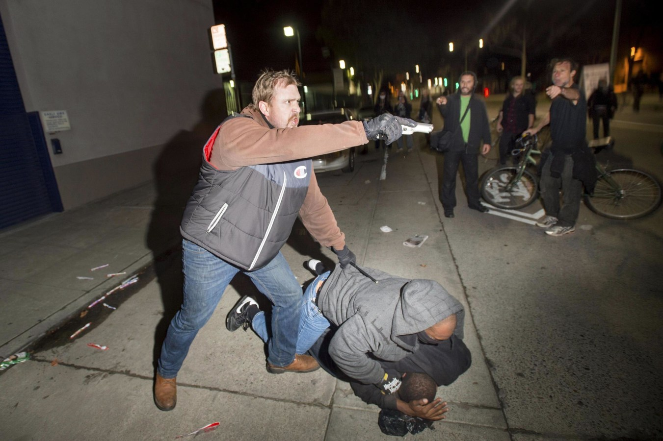Image: An undercover police officer, who had been marching with anti-police demonstrators, aims his gun at protesters after some in the crowd attacked him and his partner in Oakland