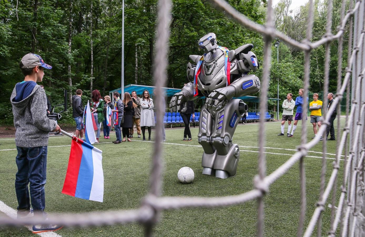 图片:俄罗斯国家足球队的支持者踢足球与泰坦机器人