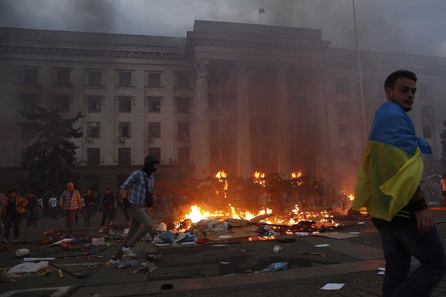 Image A protester wrapped in a Ukrainian flag walks past a burning tent c& and : fire in tent - memphite.com