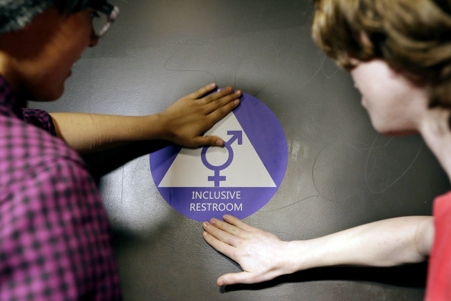 Destin Cramer and Noah Rice place a new sticker on the door at the ceremonial opening of a gender neutral bathroom at Nathan Hale high school. Transgender Bathroom Access to Extend to All Federal Buildings