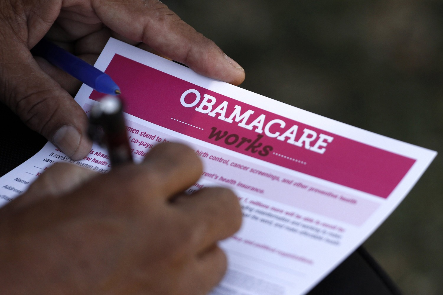 Image A Man Fills Out An Information Card During An Affordable Care Act Outreach Event