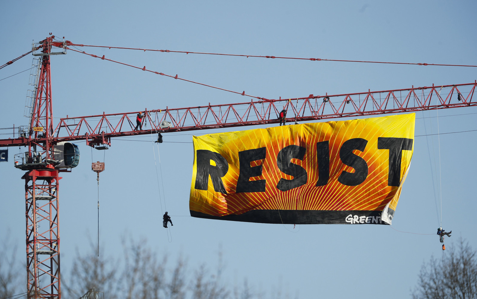 Image Protesters unfurl a banner that reads