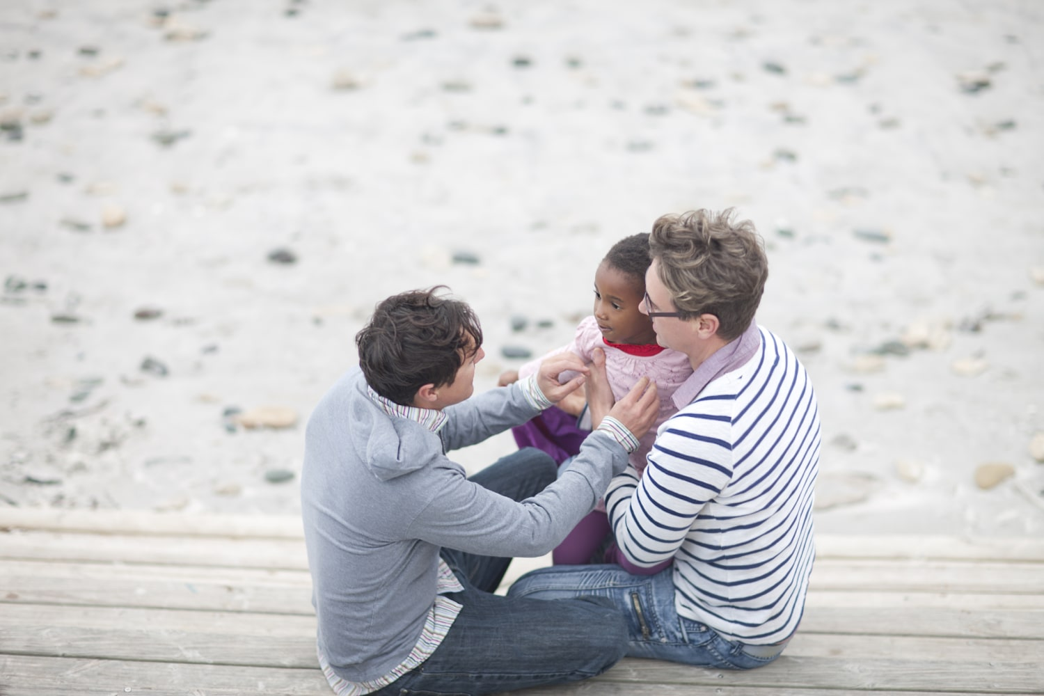 Gay Couple And Child At Beach