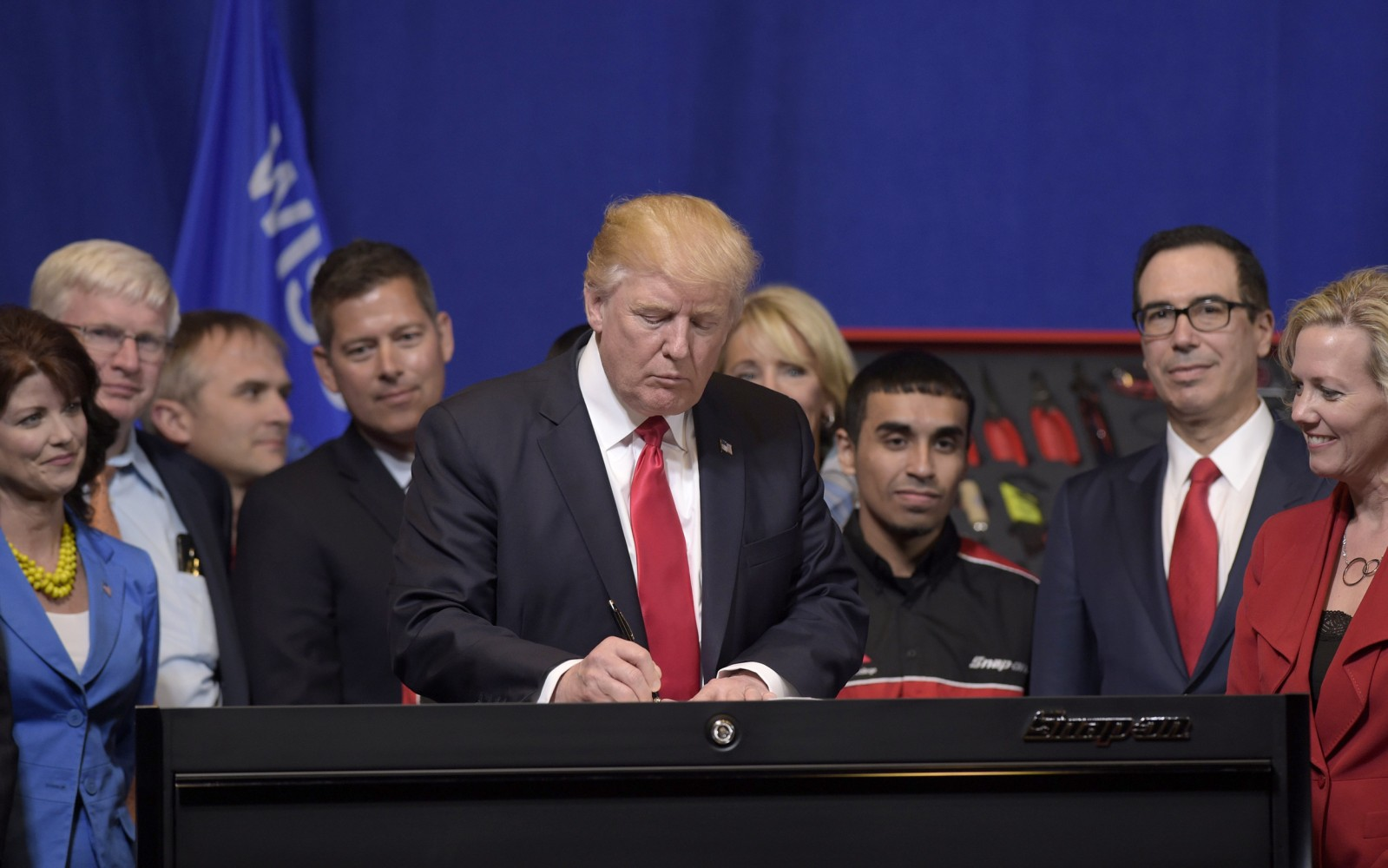 Image President Donald Trump signs an executive order during a visit to the headquarters of tool manufacturer Snap-on Inc. in Kenosha Wisconsin