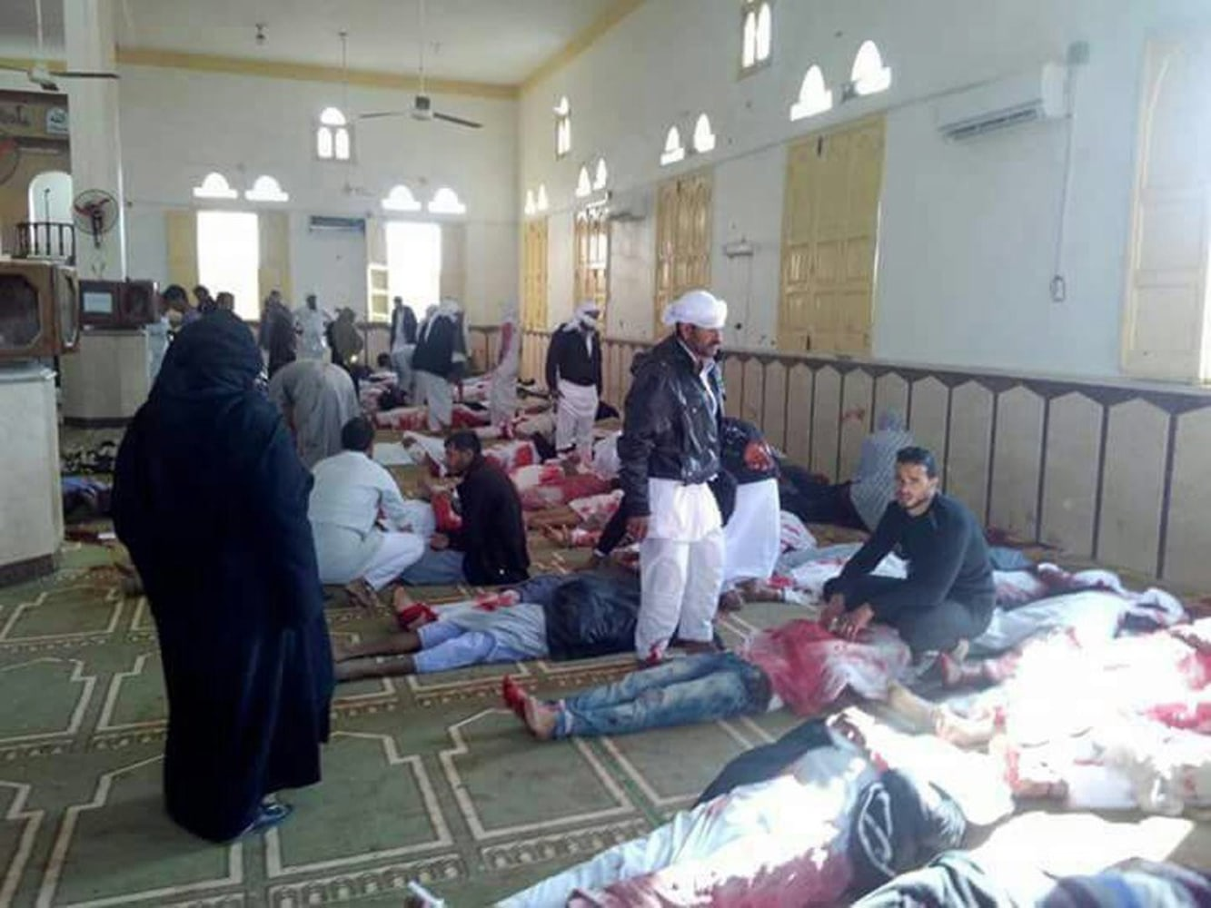 Image People sit next to bodies of worshippers