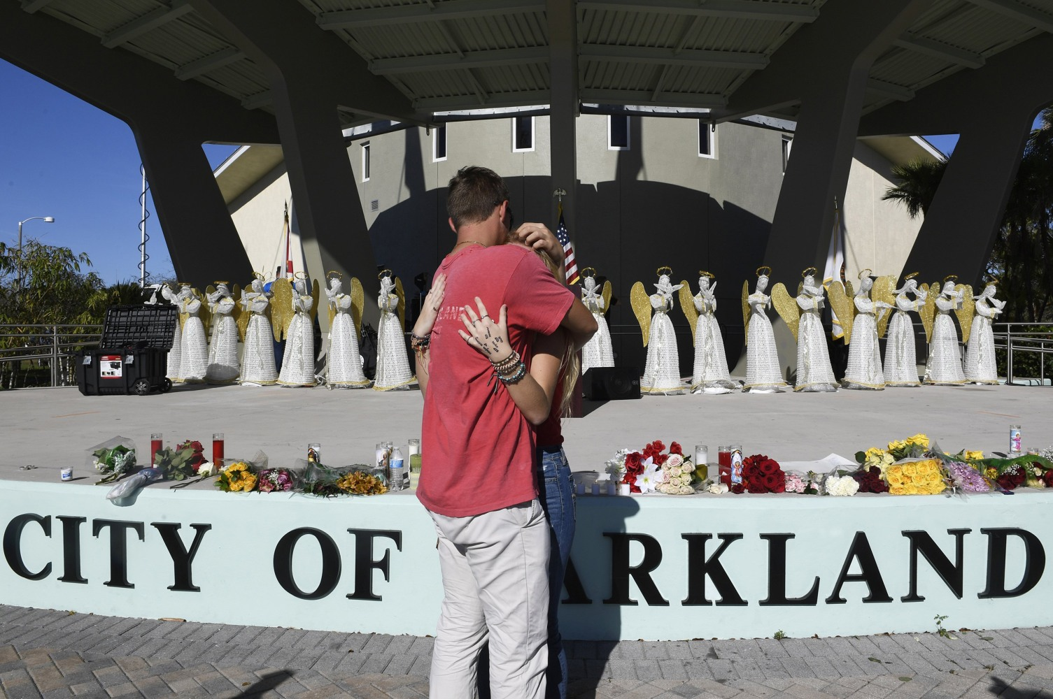 Zack King, left, comforts friend Mychal Bradley in front of 17 angels representing those who died at the Marjory Stoneman Douglas High School shooting in Parkland, Florida. Taimy Alvarez / AP