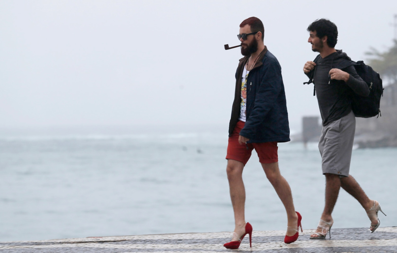 High Heeled Protest Men Strut Along The Beach Ahead Of