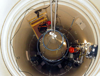 Image: A Malmstrom Air Force Base missile maintenance team removes the upper section of an ICBM at a Montana missile site.