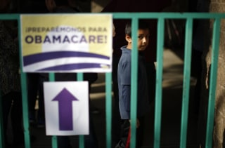 Image: A boy waits in line at a health insurance enrollment event in Cudahy, California