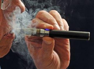 A smoker puffs on an e-cigarette.