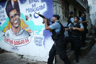 Image: Police patrol next to a mural of dancer Douglas Rafael da Silva Pereira in the pacified Pavao-Pavaozinho community