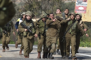 Image: Israeli soldiers carry a wounded comrade on a stretcher near Israel's border with Lebanon